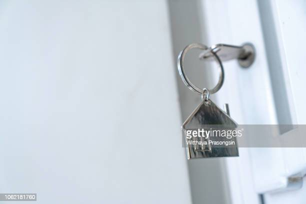 house key in the door - mortgage stock pictures, royalty-free photos & images