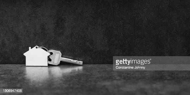 house key on dark textured background - finanzas y economía fotografías e imágenes de stock