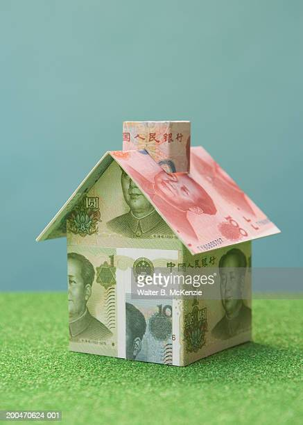 House made of Chinese Yuan currency on artificial turf
