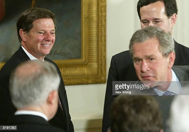 House Majority Leader Tom DeLay looks at US President George W Bush as he greets guests after signing the Unborn Victims of Violence Act April 1 2004...