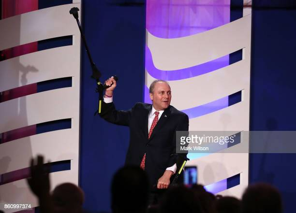 House Majority Whip Steve Scalise holds up his crutch as he walks off stage after speaking during the annual Family Research Council's Values Voter...