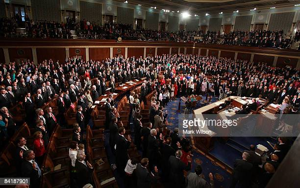House members raise their right hands during a mock swearing-in ceremony inside the House Chamber in the U.S. Capitol January 6, 2009 in Washington,...