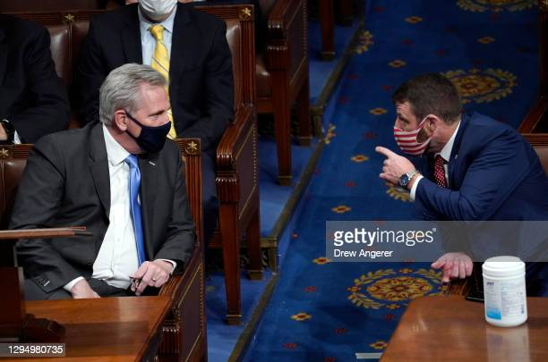 House Minority Leader Kevin McCarthy talks with U.S. Rep. Markwayne Mullin in the House Chamber during a reconvening of a joint session of Congress...