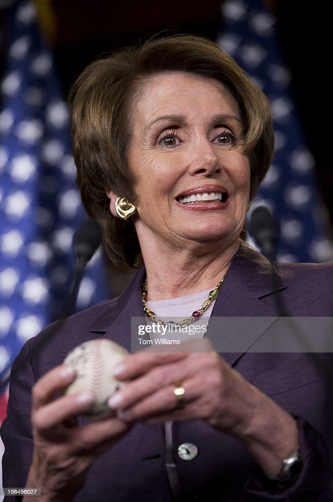House Minority Leader Nancy Pelosi, D-Calif., holds a baseball signed by the 2012 World Champion San Francisco Giants and past players for the team, during her weekly news conference in the Capitol Visitor Center.