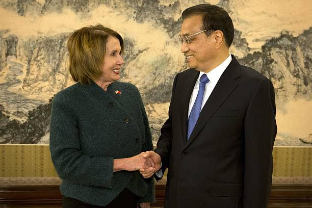 House Minority Leader Nancy Pelosi of California shakes hands with Chinese Premier Li Keqiang as she arrives for a bilateral meeting at the...