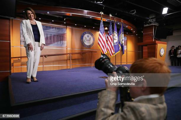 House Minority Leader Nancy Pelosi pauses while Archer Somodevilla takes a photograph during her weekly news conference at the US Capitol Visitors...