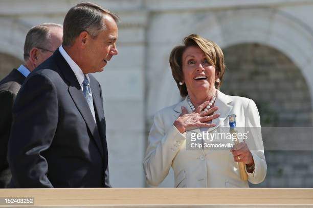 House Minority Leader Nancy Pelosi reacts after Speaker of the House John Boehner finishes driving her nail with one stroke during the First Nail...