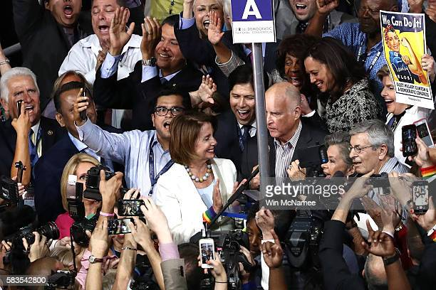 House Minority Leader Nancy Pelosi stands with California Governor Jerry Brown as the California delegation cast their votes during roll call on the...