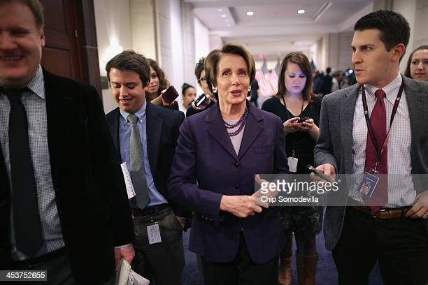 House Minority Leader Nancy Pelosi talks with reporters after a caucus meeting in the Capitol Visitors Center December 5 2013 in Washington DC House...