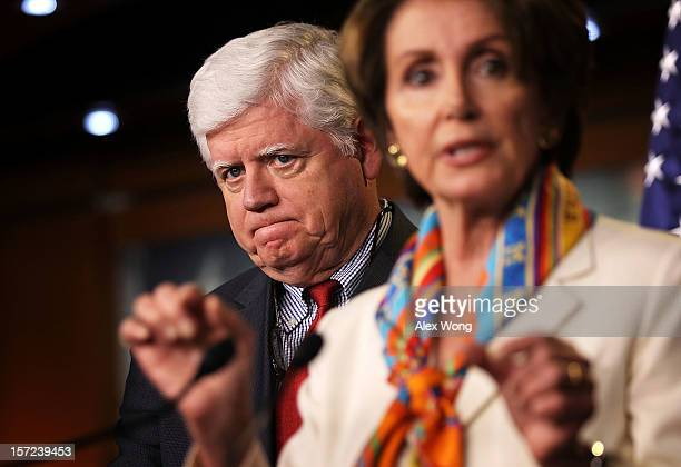 S House Minority Leader Rep Nancy Pelosi speaks as Rep John Larson listens during a news conference November 30 2012 on Capitol Hill in Washington DC...
