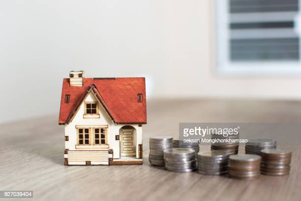 House model and coin money on table for finance and banking concept.