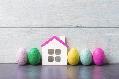 House model and painted Easter eggs over white wooden background. 1138017185