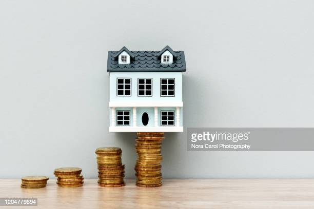 house model on top of stack of coins - ��couter photos et images de collection