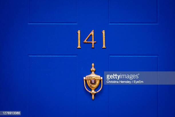 house number 141 on a blue wooden front door - door stock pictures, royalty-free photos & images