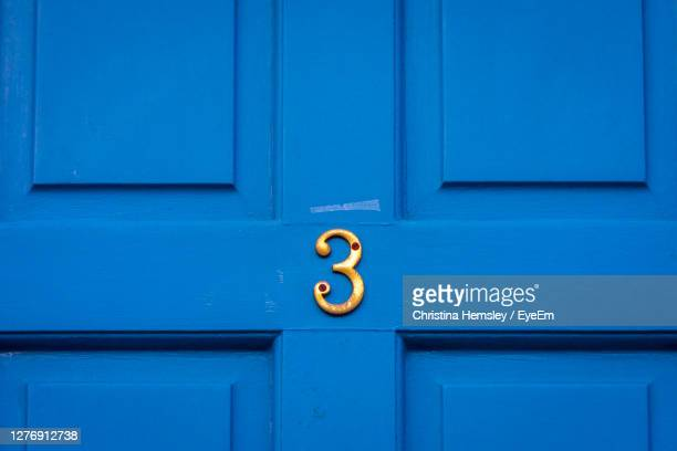 house number 3 on a blue wooden front door - number 3 stock pictures, royalty-free photos & images