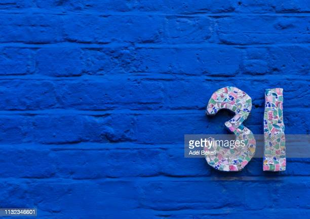 house number 31 on blue brick wall - number 31 stock pictures, royalty-free photos & images