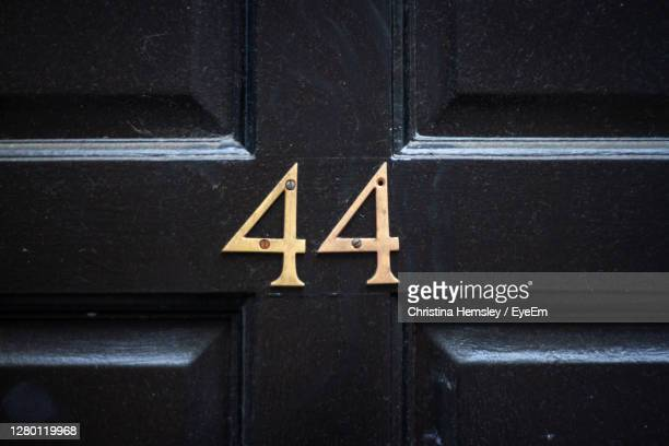 house number 44 on a dark wooden front door in london - elegance stock pictures, royalty-free photos & images