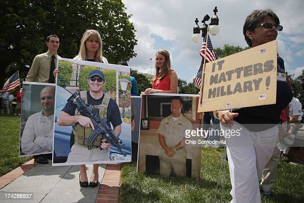 House of Representatives interns carry photographs of former Navy SEAL members Tyrone Woods and Glen Doherty and U.S. Foreign Service IT specialist...