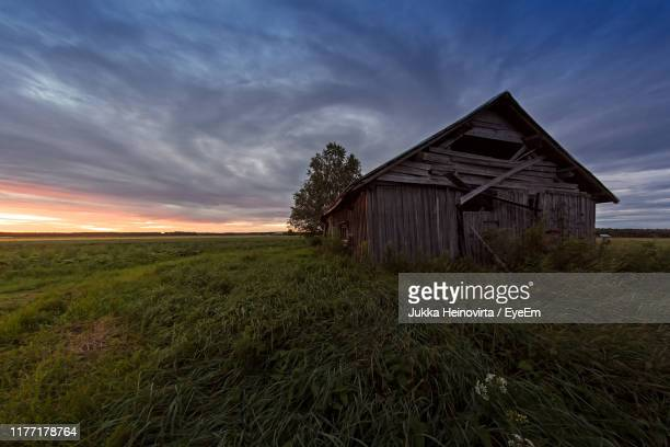 house on field against sky during sunset - heinovirta stock photos and pictures