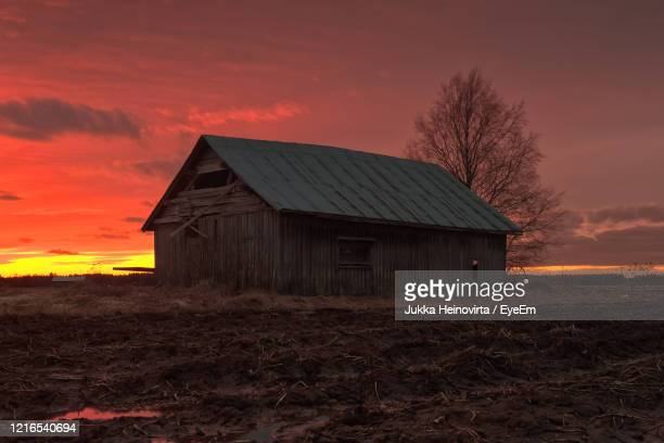 house on field against sky during sunset - heinovirta stock pictures, royalty-free photos & images
