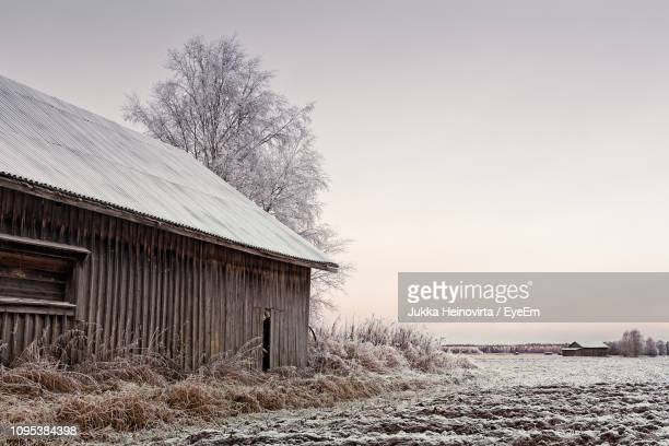 house on field against sky during winter - heinovirta stock photos and pictures