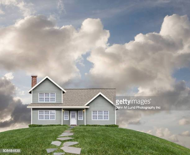 house on grassy hill - hill stock pictures, royalty-free photos & images
