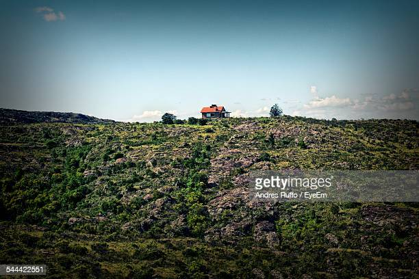house on grassy hills against sky - andres ruffo stock pictures, royalty-free photos & images