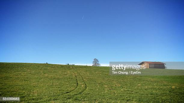 House On Grassy Landscape Against Clear Blue Sky