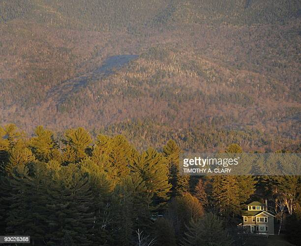 A house on Mirror Lake in Lake Placid New York is dwarfed by the trees and mountain range behind it November 12 2009 Lake Placid is hosting Skate...
