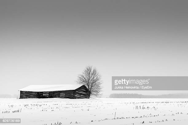house on snow covered field against clear sky - heinovirta stock pictures, royalty-free photos & images