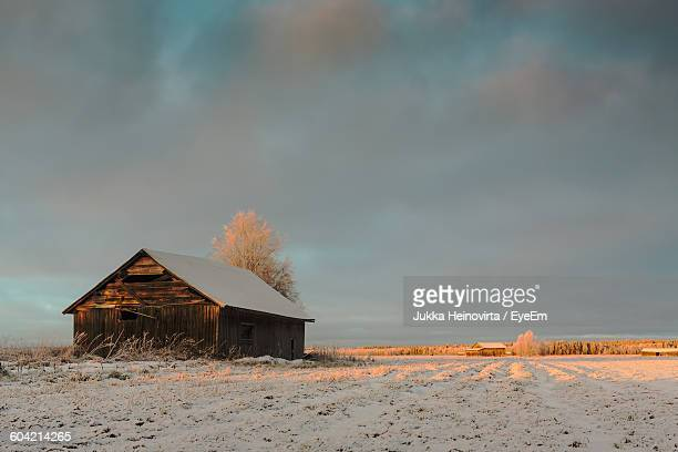 house on snow covered field against sky - heinovirta stock pictures, royalty-free photos & images