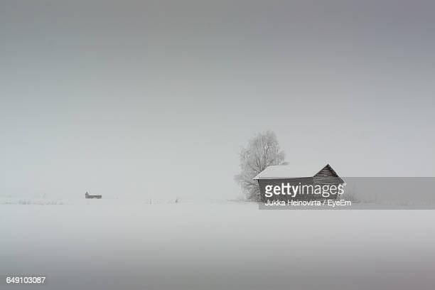 house on snowy field against clear sky during winter - heinovirta stock pictures, royalty-free photos & images