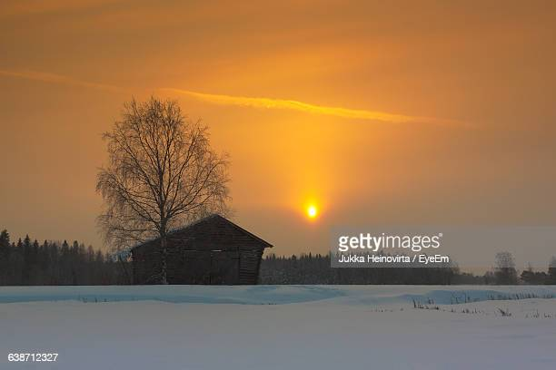 house on snowy field against sky during sunset - heinovirta stock pictures, royalty-free photos & images