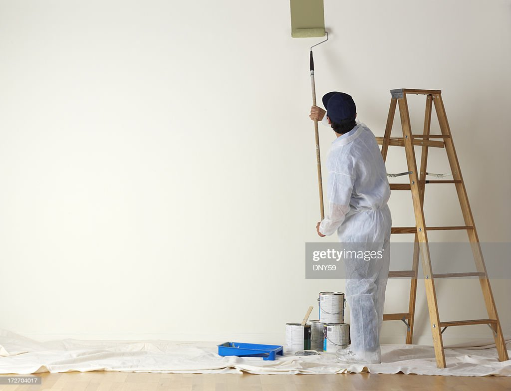 House painter beginning to paint a large wall : Stock Photo
