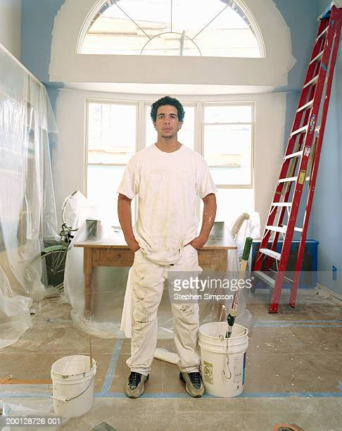 House painter in room covered protective tape and plastic, portrait