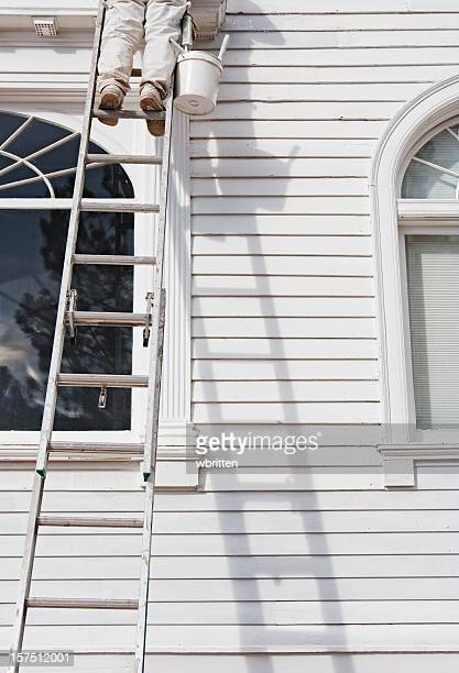 House painter on a ladder leaning on a white house exterior