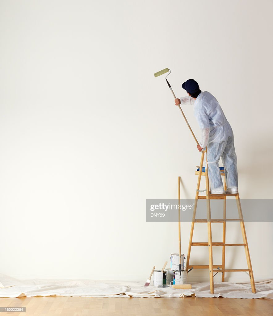 House painter standing on ladder painting a large wall : Stock Photo