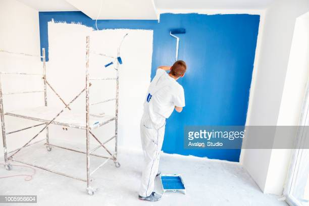 House painters beginning to paint a large blue wall