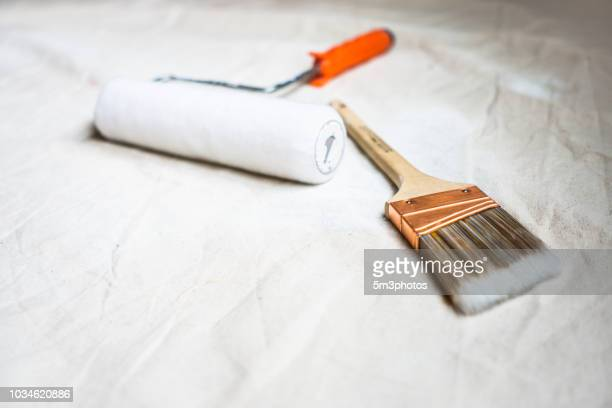 House painting DIY home improvement flat lay brush roller on drop cloth