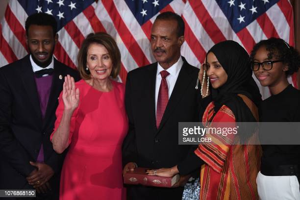 US House Representative Ilhan Omar DMN with her hand on the Quran participates in a ceremonial swearingin with Speaker of the House Nancy Pelosi DCA...