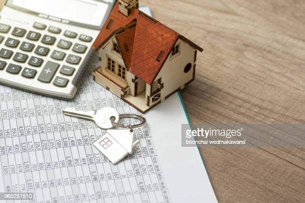 house resting on calculator concept for mortgage calculator, home finances or saving for a house - house stock pictures, royalty-free photos & images