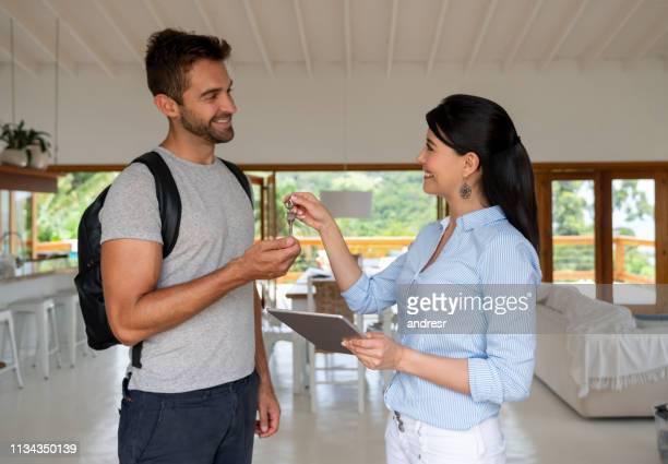 casa compartiendo anfitriona manejando las llaves de un huésped feliz - anfitriona de la fiesta fotografías e imágenes de stock