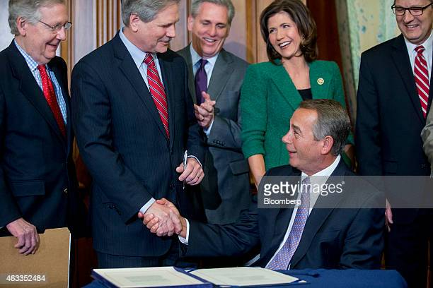 House Speaker John Boehner, a Republican from Ohio, bottom, shakes hands with Senator John Hoeven, a Republican from North Dakota, after signing the...