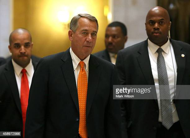 House Speaker John Boehner is escorted by his security detail as he walks to the House chamber before a vote at the US Capitol November 14 2014 in...