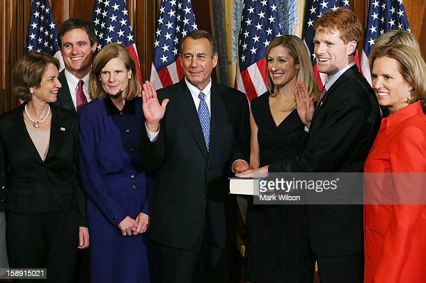 House Speaker John Boehner swears in US Rep Joseph Kennedy as his fiance Lauren Ann Birchfield holds a bible during a reenactment ceremony after the...