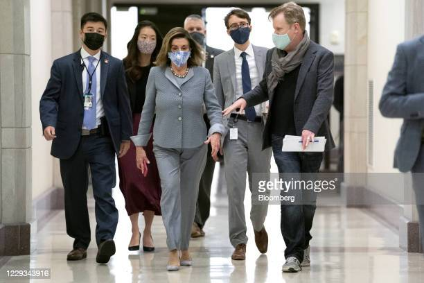 US House Speaker Nancy Pelosi a Democrat from California center wears a protective mask while exiting a news conference at the US Capitol in...