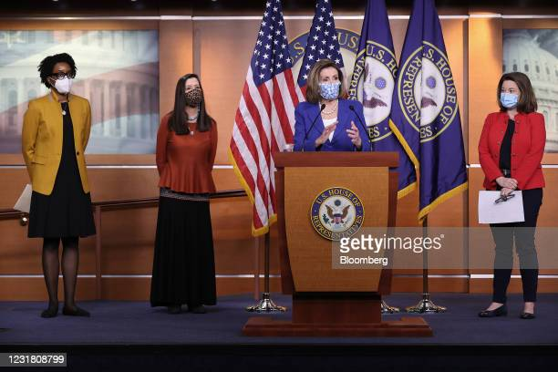 House Speaker Nancy Pelosi, a Democrat from California, center, wears a protective mask while speaking during a news conference with Representatives...