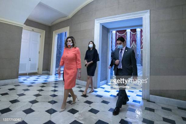 US House Speaker Nancy Pelosi a Democrat from California left wears a protective mask while walking to her office from the House floor after a moment...