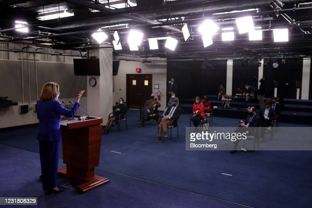 House Speaker Nancy Pelosi, a Democrat from California, left, wears a protective mask while speaking during a news conference at the U.S. Capitol in...
