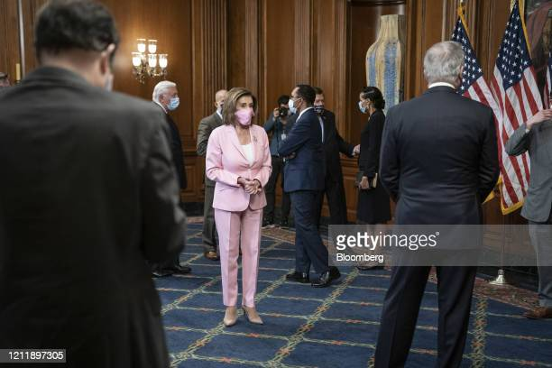 House Speaker Nancy Pelosi, a Democrat from California, wears a protective mask while participating in a swearing-in ceremony for...